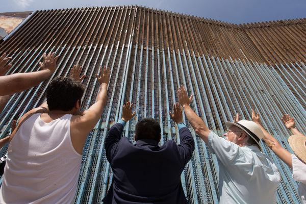 Prestene Joel Hortiales (i blått i midten) og David Farley (til høyre for Hortiales) sammen med medlemmer av grensekirken i Tijuana i Mexico. De løfter sine hender ved gjerdet som markerer grensen mellom Mexico og USA. Foto: Mike DuBose, UMNS